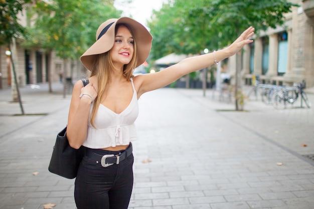屋外でタクシーをキャッチしている幸せな若い女性