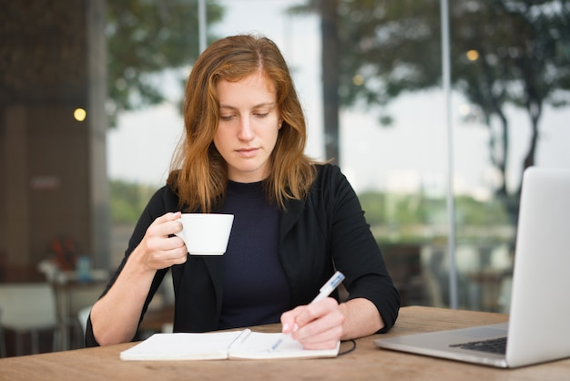 コーヒーカップを書く真剣な学生