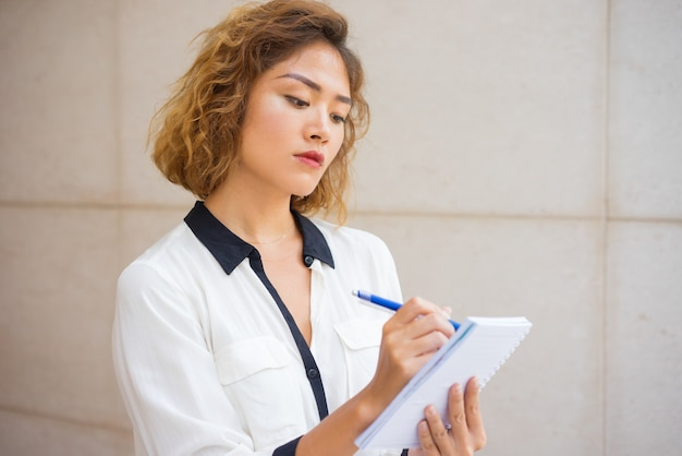 注意深い若いアジアの女性がノートを作る