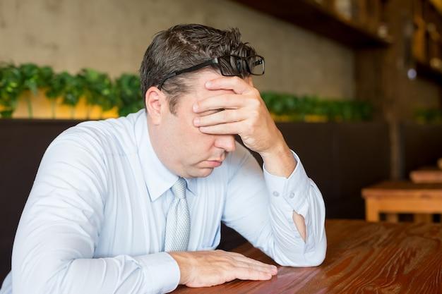 カフェのラップトップで働くストレスのあるビジネスマン