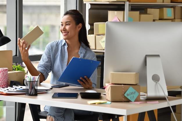 若いアジア女性起業家ビジネスオーナーのオンラインショッピングのために自宅で仕事