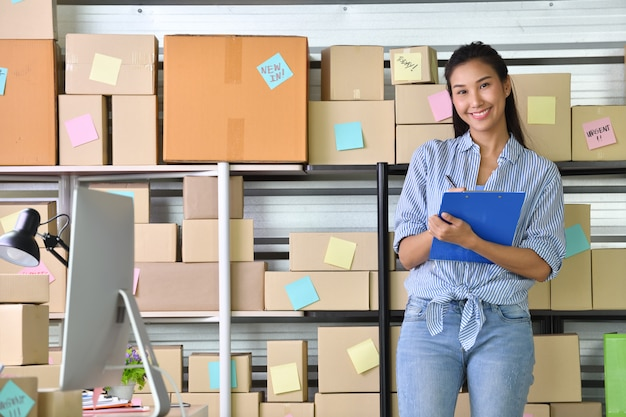 Молодая азиатская женщина-предприниматель, владелец бизнеса, работающий дома для покупок в интернете и готовящий пакетный продукт