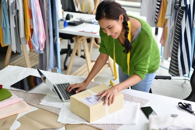 Молодая азиатская женщина предприниматель / модельер работает в студии и упаковки и отправки продукта