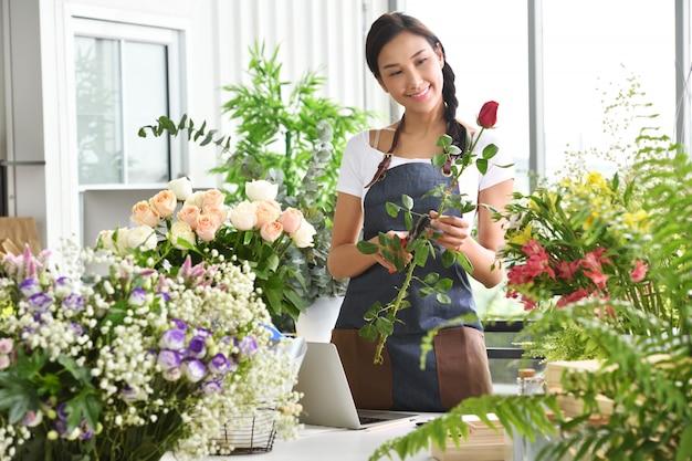 Молодая азиатская женщина-предприниматель / владелец магазина / флорист мелкого цветочного магазина