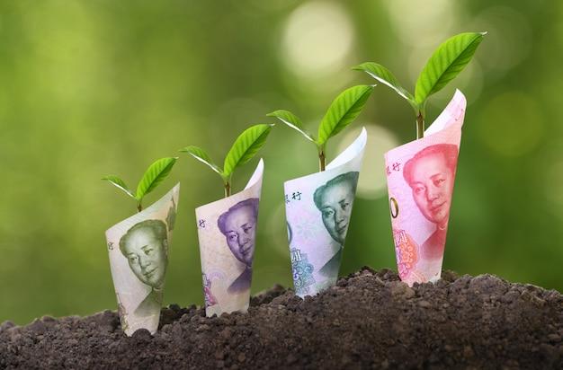 工場、ビジネス、節約、成長、経済概念の上に成長している中国元紙幣の画像