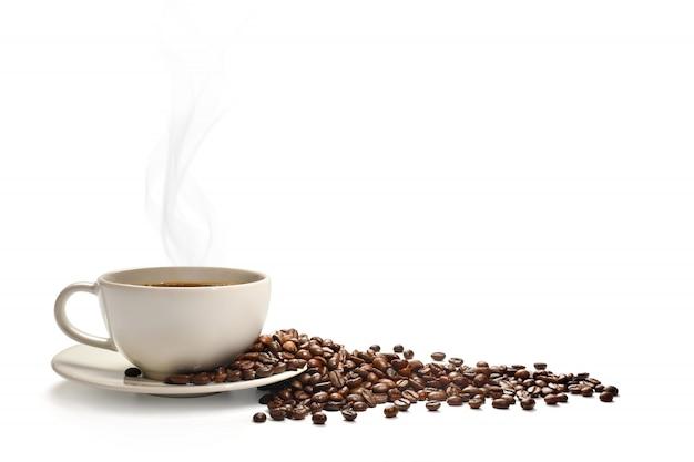 煙と白で隔離されるコーヒー豆とコーヒーのカップ