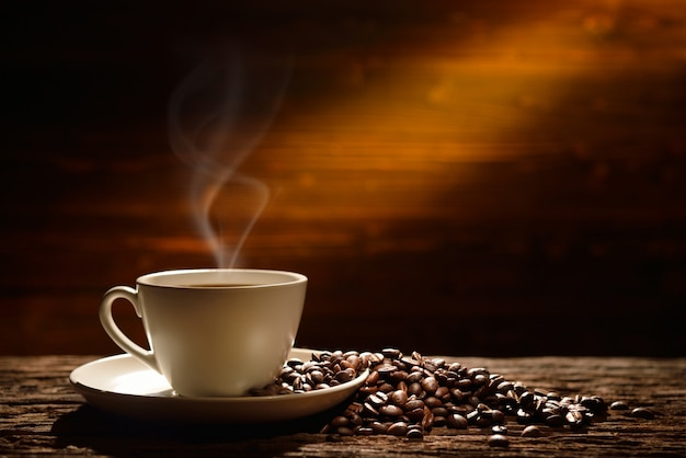 コーヒーカップと古い木製の背景にコーヒー豆