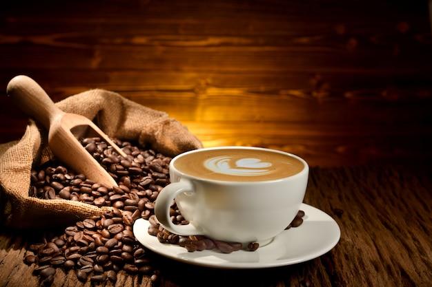 一杯のコーヒーカフェラテと古い木製の背景にコーヒー豆
