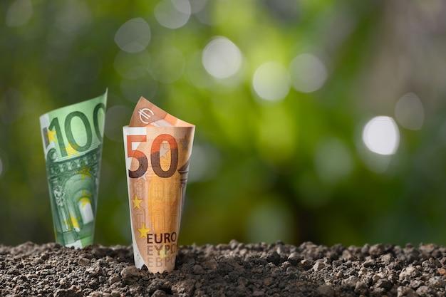 ビジネス、貯蓄、成長、経済概念のための土の上にユーロお金紙幣のイメージ