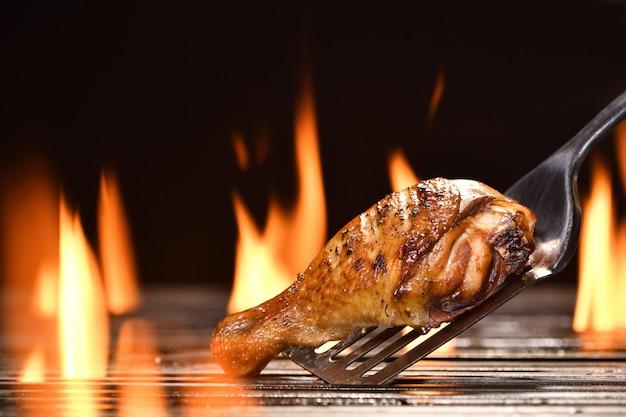 燃えるようなグリルで様々な野菜を使ったグリルドチキンレッグ
