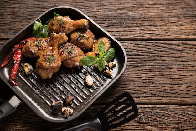 古い木製の背景上の鍋で様々な野菜と鶏のグリル脚