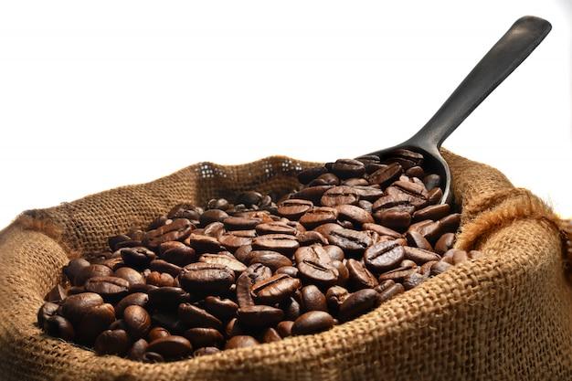 黄麻布の袋の白い背景で隔離のコーヒー豆の山の上のスプーンでコーヒー豆