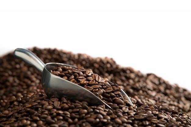 白い背景で隔離のコーヒー豆の山の上のスプーンでコーヒー豆