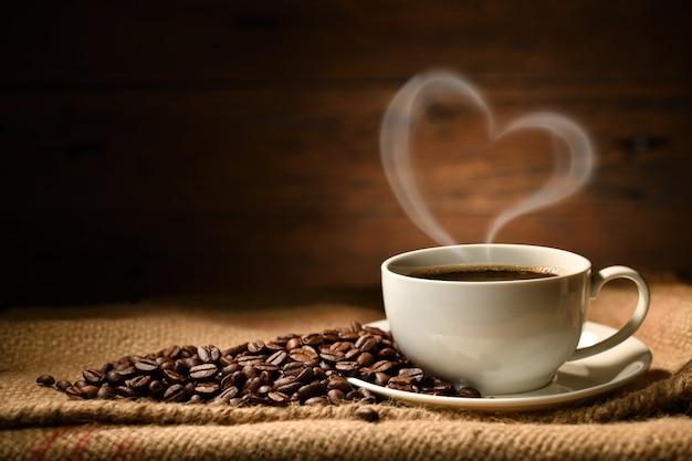 Чашка кофе с сердцем в форме дыма и кофейные зерна на мешковине на старых деревянных фоне