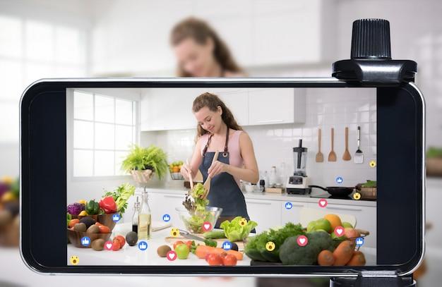 Молодая женщина-блогер, блогер и онлайн-авторитет в прямом эфире транслируют кулинарное шоу в социальных сетях с помощью смартфона
