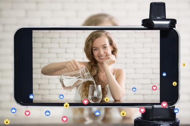 Молодая женщина-блогер, блогер и онлайн-авторитет в прямом эфире транслируют здоровый образ жизни в социальных сетях с помощью смартфона