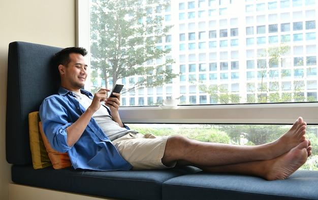 自宅のソファーに座りながら携帯電話で話している若い男