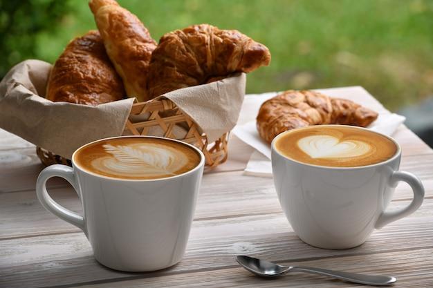 一杯のコーヒーカフェラテとクロワッサンの白い木製のテーブル