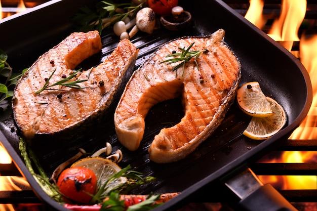 Лосось на гриле с различными овощами на сковороде на гриле