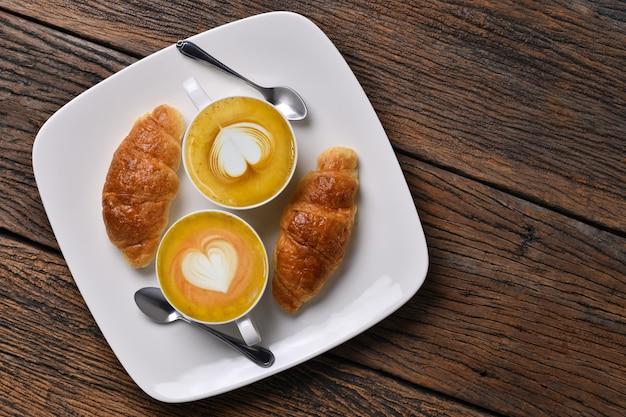 古い木製のテーブルにコーヒーカフェラテとクロワッサンのトップビューカップ