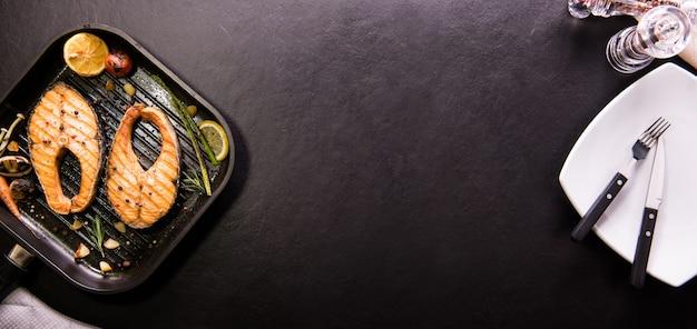 Лосось на гриле с различными овощами на сковороде на черном камне
