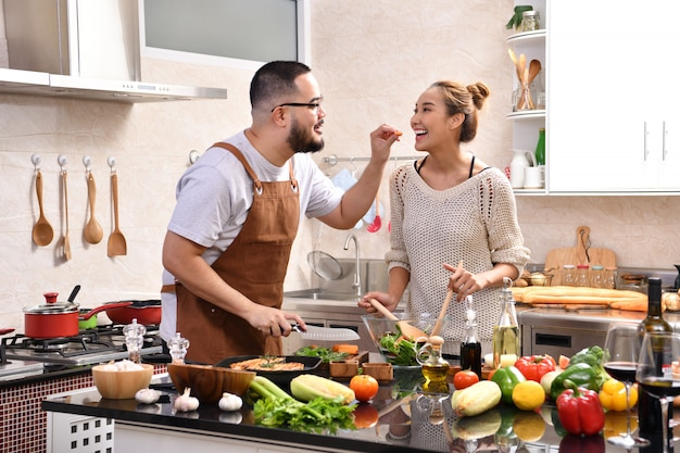 Любящие молодые азиатские пары готовя в кухне делая здоровую еду совместно чувствуя потеху