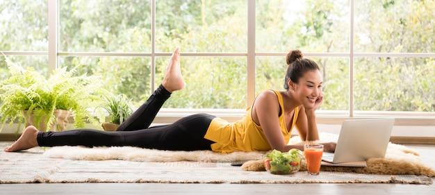 サラダを食べて、ラップトップコンピューターを見て床に横たわって健康的なアジアの女性