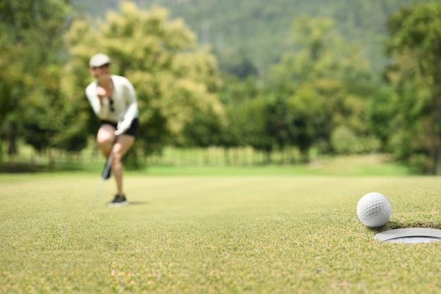 ゴルフグリーン上のゴルフボールの後応援女性ゴルファー