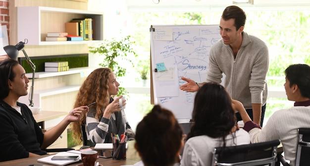 オフィスでの仕事を議論する創造的なビジネスの実業家のグループ