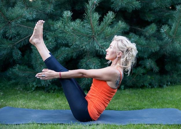 Фитнес женщина делает подъем ноги на траве на открытом воздухе