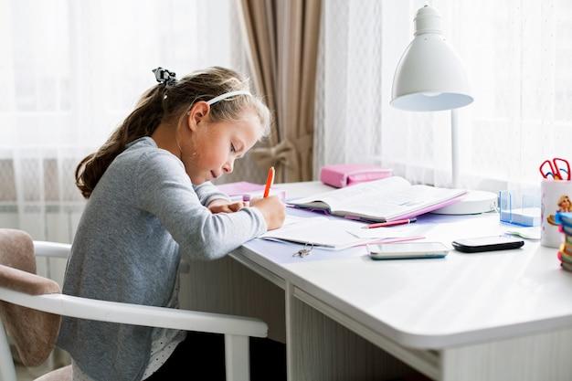 練習帳に何かを書く小さな学校の女の子