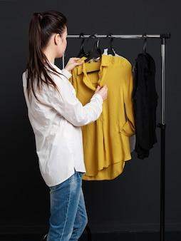 顧客は服を選びます。白いブラウスの若い女性、
