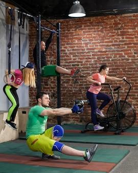 人々はクロスフィットジムでトレーニングしています