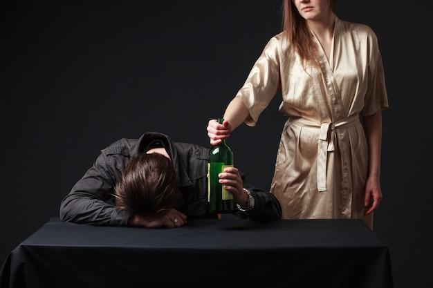アルコール中毒、男性からアルコールのボトルを削除する女性
