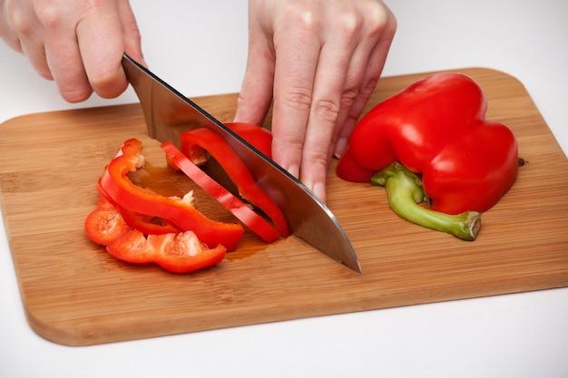 木の板にナイフで赤唐辛子を切る