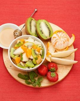 新鮮な果物。静物。果物のセットと、木の板にフルーツサラダと蜂蜜、