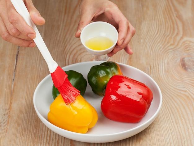 Приготовление перца - мужские руки смазывают овощи маслом