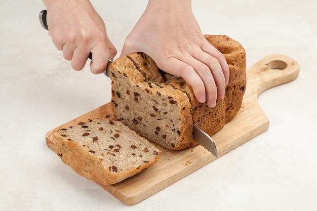 女性の手は木製のテーブルボードにナイフで焼きたてのパンをスライスしています
