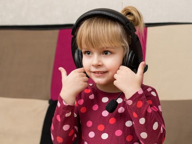 笑みを浮かべてヘッドフォンで小さなブロンドの女の子
