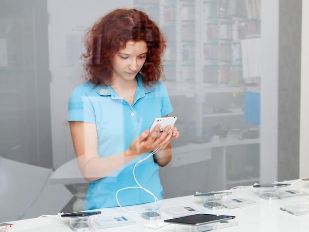 Женщина выбирает смартфон в магазине