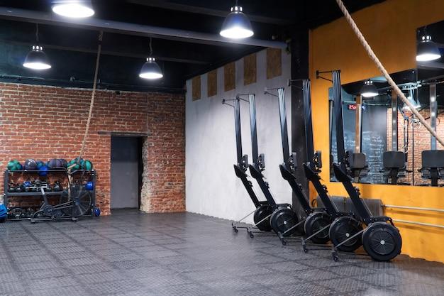 Современный интерьер фитнес-зала с гребными тренажерами и спортивным оборудованием