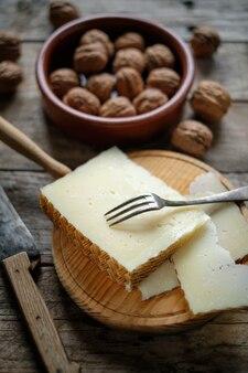 マンチェゴチーズと素朴な木製のテーブル上のナッツ