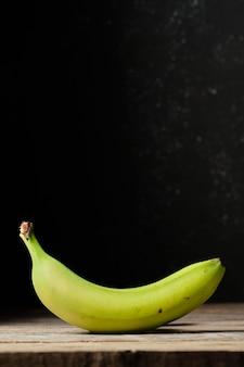 Зеленый банан с черным фоном в вертикальном