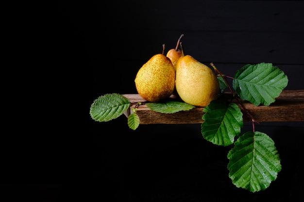 Спелые желтые груши и зеленые листья на черном