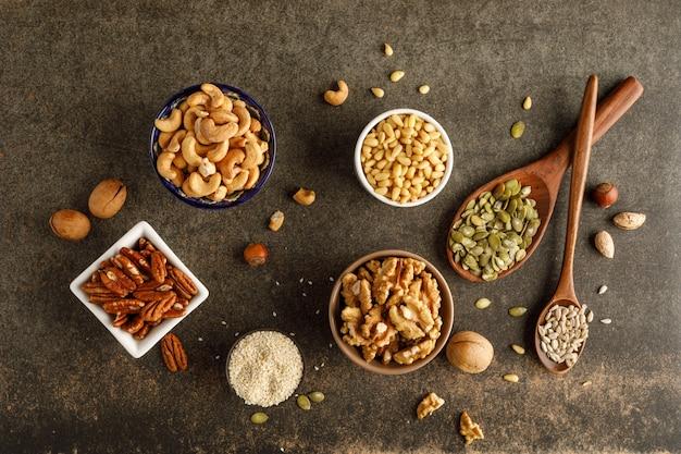 Разные виды орехов в мисках. вид сверху
