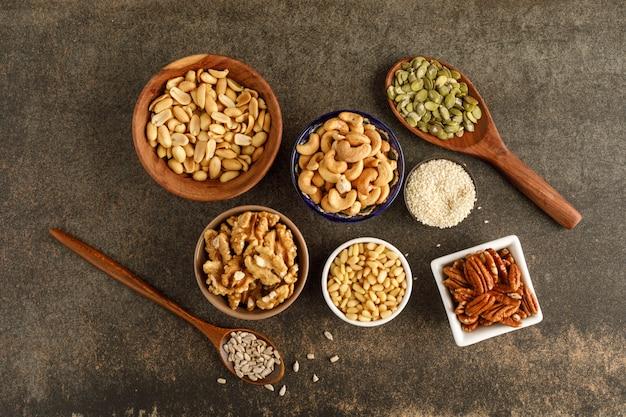 Разные виды орехов в мисках. вид сверху. копировать пространство
