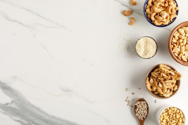 Рама изготовлена из разных видов орехов в мисках. вид сверху. копировать пространство
