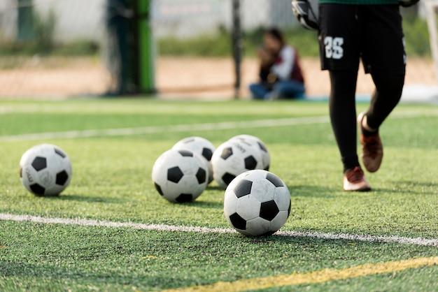 Тренировочный мяч на зеленом футбольном поле