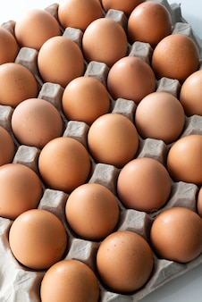 Закройте куриные яйца в картонной коробке