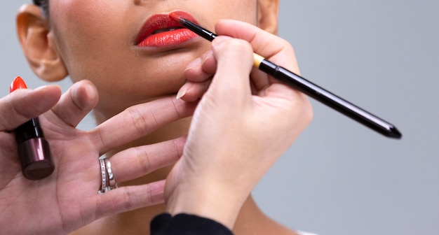 Рука визажиста рисует помаду на губе